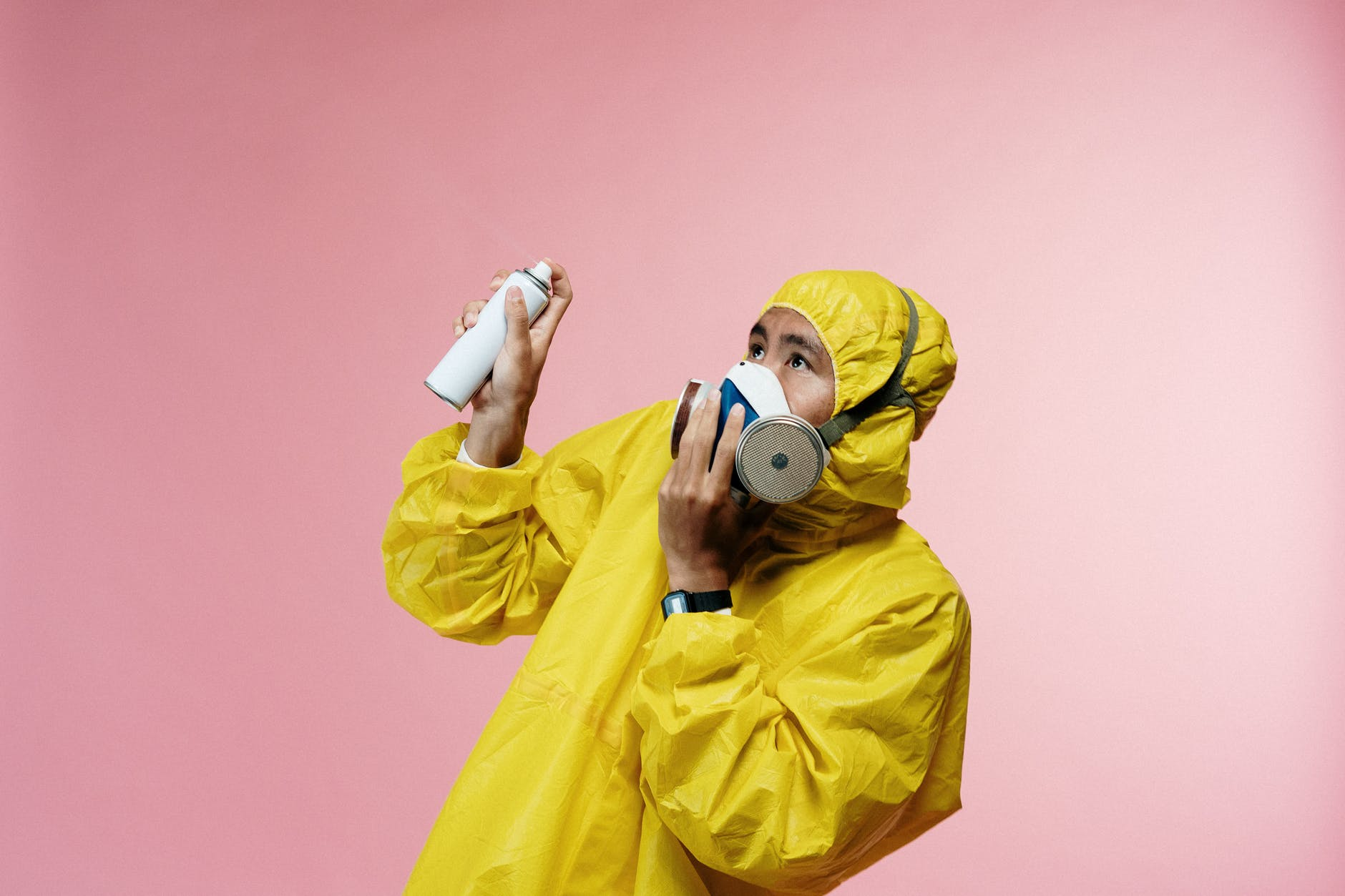 person in coveralls holding spray bottle